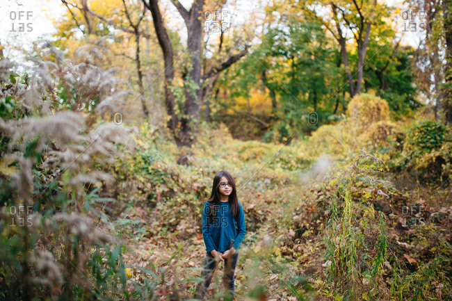 Young girl standing in the forest during fall