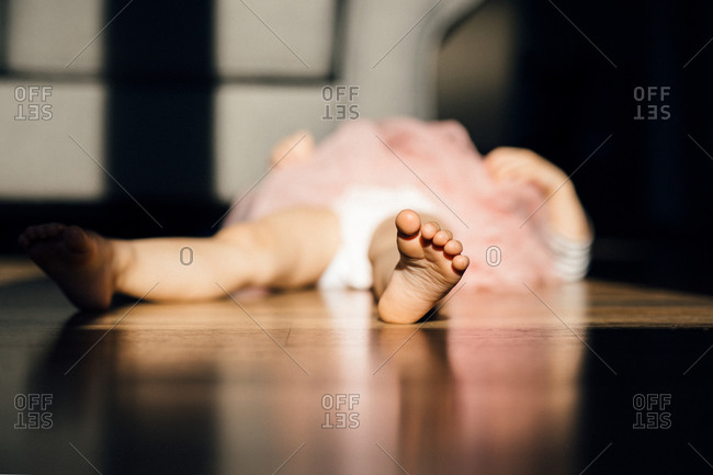 Little girl in a pink tutu lying on the floor