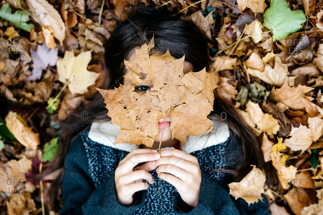 Little girl lying in fallen leaves with one covering her face
