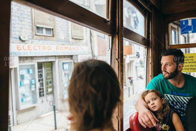Man riding in a tram with his daughter through Lisbon, Portugal
