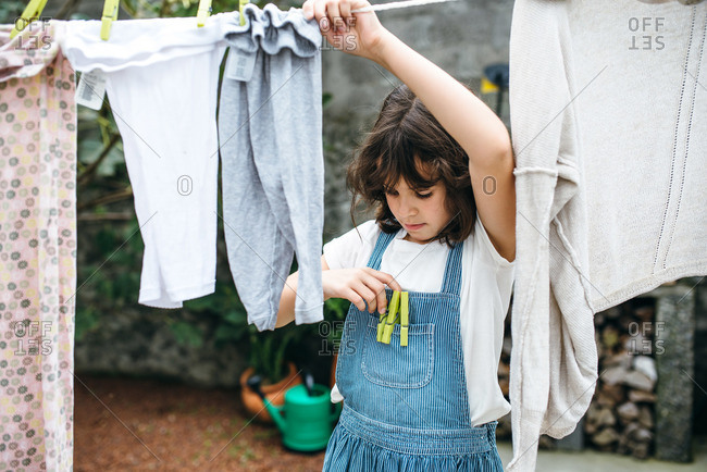Little girl grabbing clothespin to hang pants on a clothesline