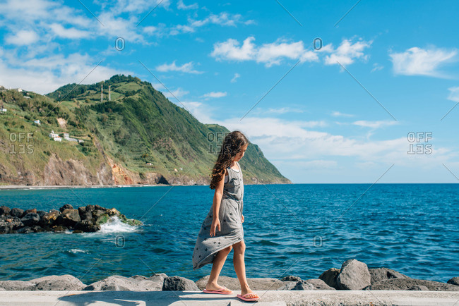 Girl walking along the coast of Sao Miguel Island, Portugal