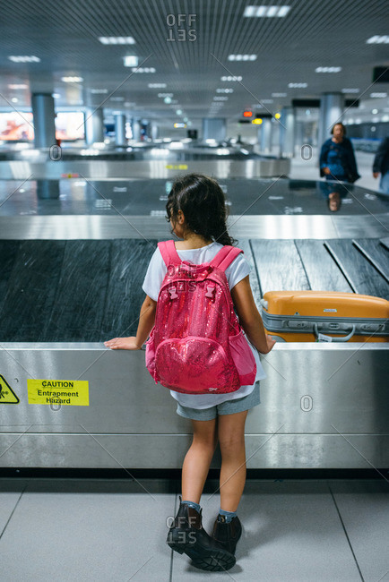 Girl standing by conveyer belt waiting for luggage at an airport
