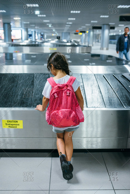 Girl standing by conveyer belt waiting for bags at an airport