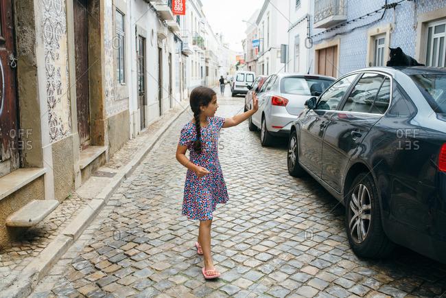 Girl waving at a stray cat, Portugal