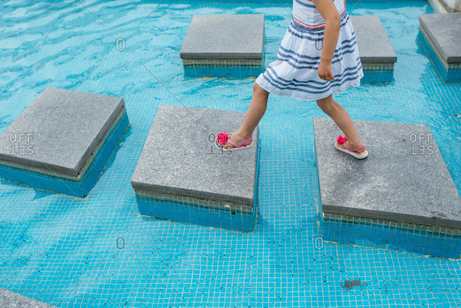 Girl walking over squares in a pool