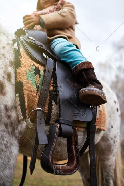Girl sitting on top of saddled horse