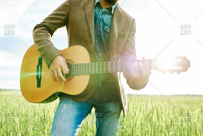 Man with guitar in a rural field
