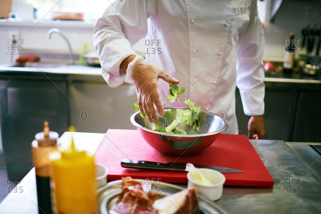 Chef tossing salad by hand