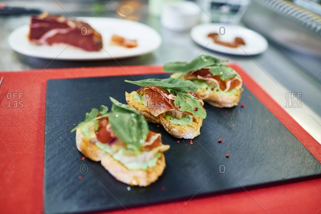 Bread slices with prosciutto, artichoke, basil