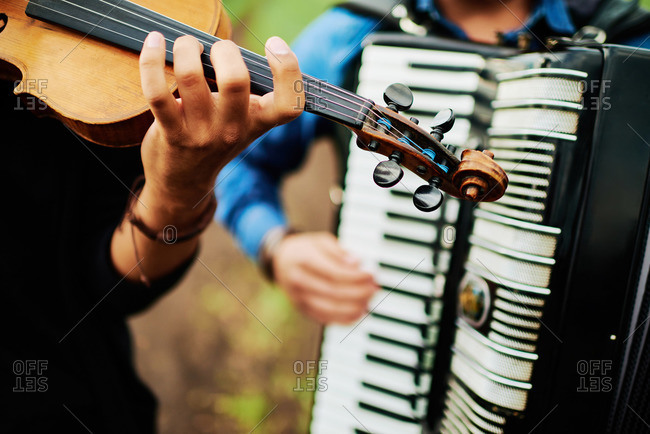 Fiddler and accordionist in rural setting