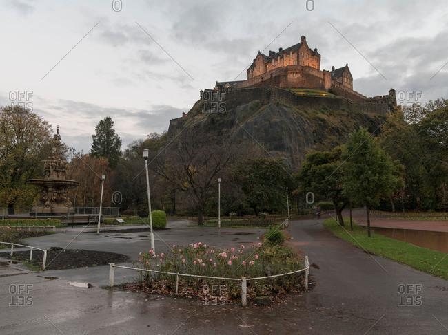 Edinburgh Castle above Princes Street Gardens and Ross Fountain in Scotland