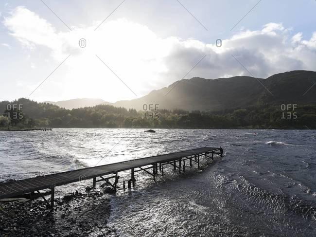 Sun shining through clouds over a dock on the way to Glencoe, Scotland