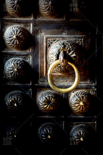 A large brass doorknob in Patan's Durbar Square among a highly crafted groupings of metalwork