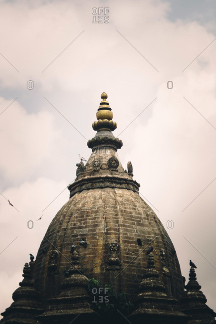 The dome of a temple is framed among clouds in Patan's Durbar Square