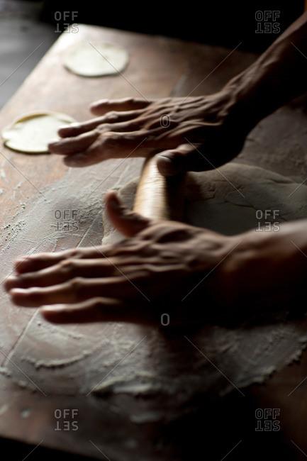 A pair of hands rolls dough to make momos, or dumplings, in Nepal