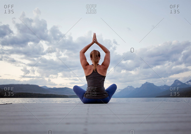 A young woman practices yoga on a dock in Montana's Glacier National Park