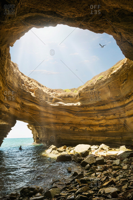 A swimmer wades in the water of a sea cave in Sunset Cliffs in San Diego, California