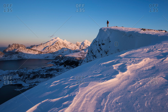 Person stands on snow covered summit of Offeroykammen in winter, Vestvagoy, Lofoten Islands, Norway