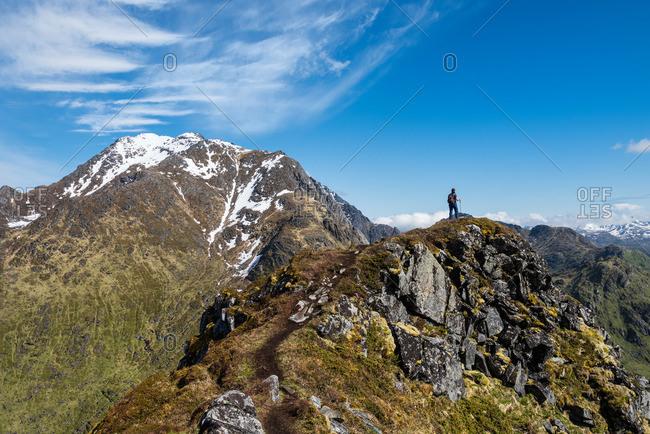 Female hiker on trail to Mannen with Himmeltindan in background, Vestvagoy, Lofoten Islands, Norway