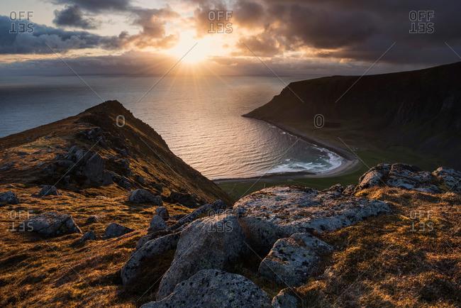 Midnight sun shines over sea from Nonstind mountain peak, Vestvagoy, Lofoten Islands, Norway