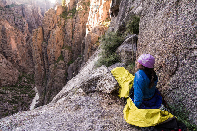Woman camping on ledge in the Black Canyon of the Gunnison, Montrose, Colorado
