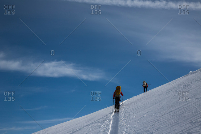 Skiers ascend a skin track at the top of a mountain in Whistler, British Columbia, Canada