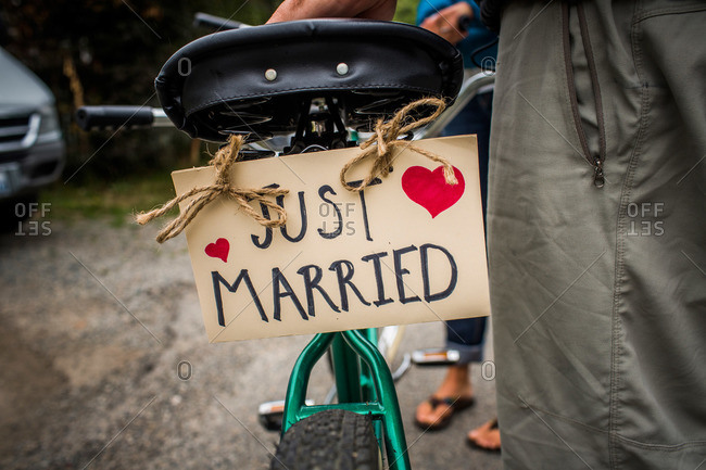 A sign reading Just Married is attached to the rear of a tandem bicycle
