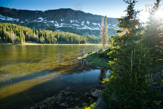 A fly fisherman fishes a high alpine lake