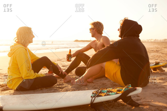 Group of surfers enjoy a drink on the beach at sunset