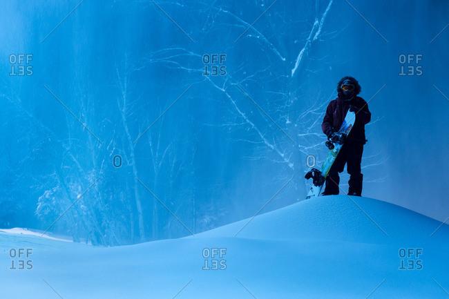Snowboarder on pile of snow in dark