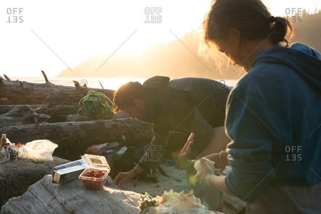 Woman cooking dinner on a beach in Oregon with friends at sunset