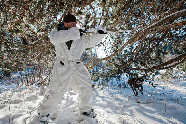 A hunter wearing a cold-weather camouflage outfit aims his rifle in preparation to shoot while his hunting dog prepares to retrieve