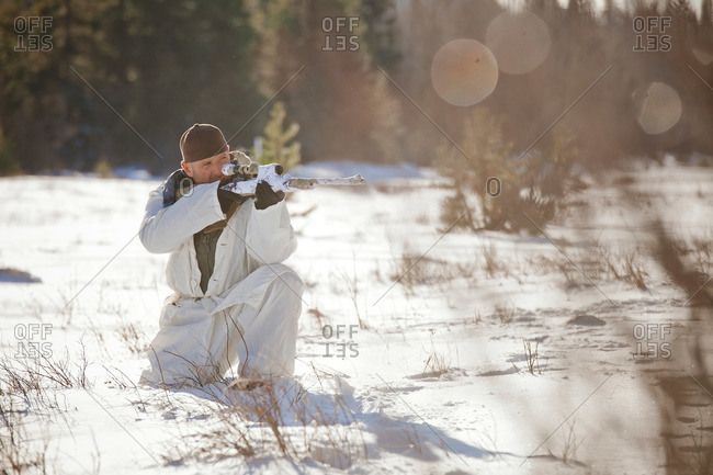 A hunter wearing a cold-weather camouflage outfit aims a rifle while crouching in a snow-covered field