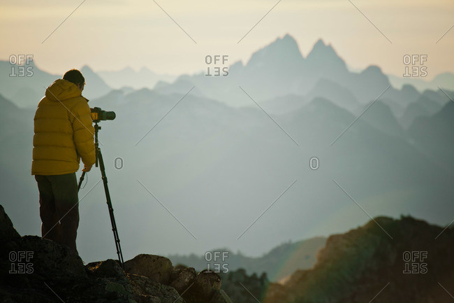 A landscape photographer uses a tripod and SLR camera to capture a picture of a neighboring mountain range