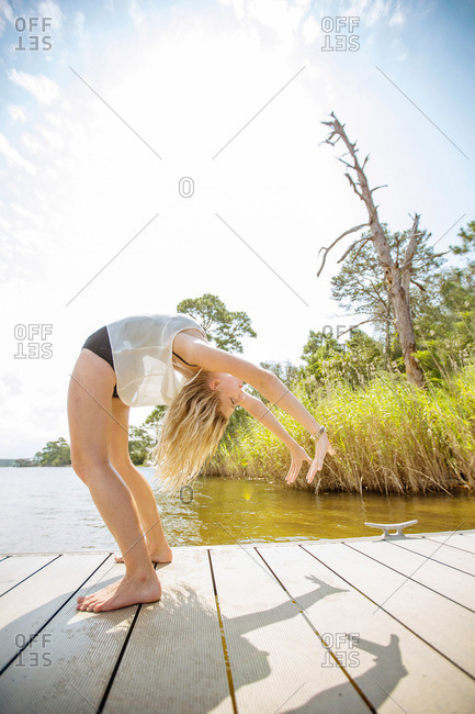 A young woman does yoga on a pier