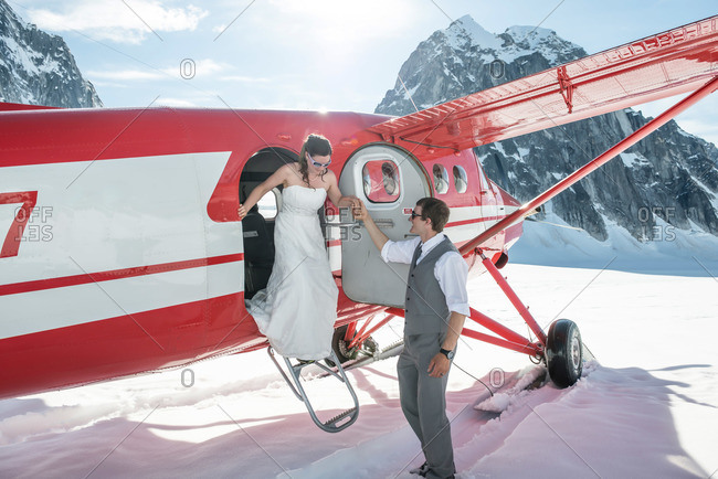 Bride and groom getting married next to a ski plane on a glacier in Denali National Park
