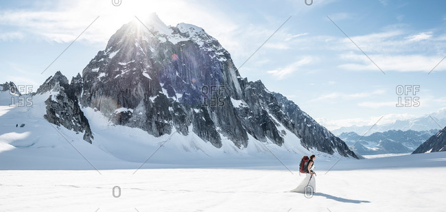 Adventurous bride carries her backpack after getting married on a glacier in Denali National Park