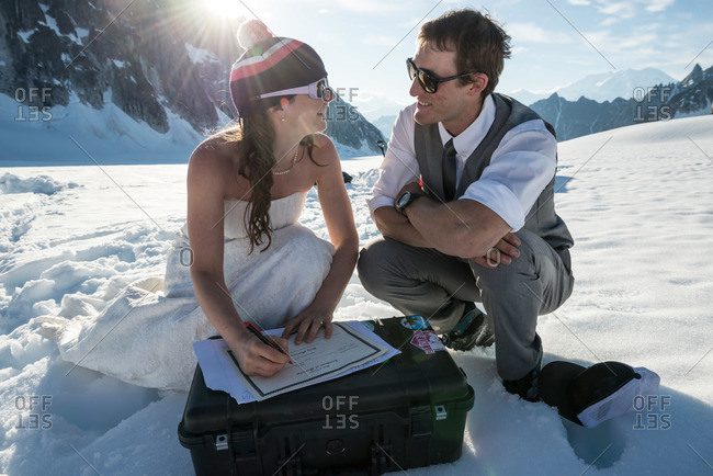 Adventurous bride and groom sign the wedding certificate after getting married on a glacier in Denali National Park