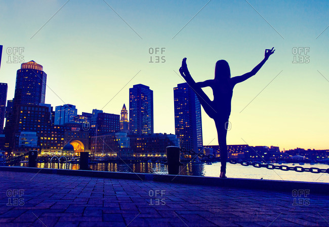 Woman doing standing yoga balance pose outside near the water facing the city