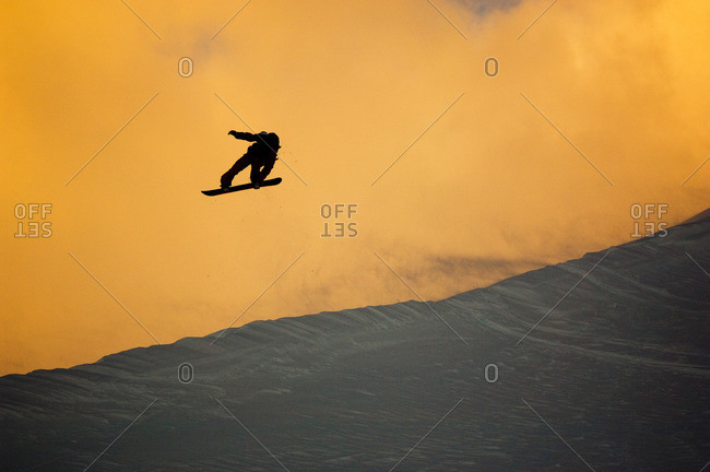 Scotty Lago jumps of a windlip at sunset in Valdez, Alaska.