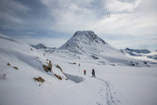 Skiers at the top of a pass with a wide expanse of the Coast Mountains ahead during the Spearhead Traverse in Whistler, British Columbia, Canada