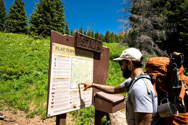 A hiker stops to read a trail map in Yampa, Colorado.