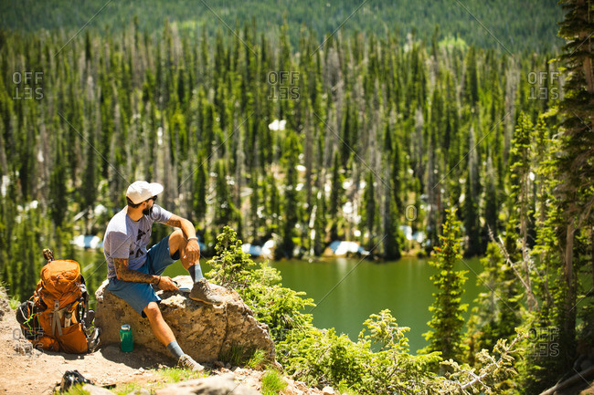A backpacker takes in the view of a high alpine lake in Yampa, Colorado.