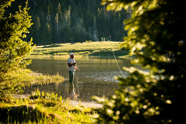A fly fisherman fishing a high alpine lake in Yampa, Colorado.
