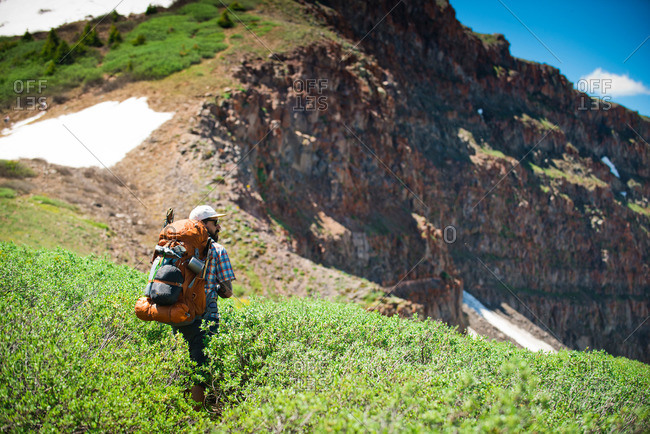 A backpacker hikes toward The Devil's Causeway in the Flat Tops Wilderness in Yampa, Colorado.