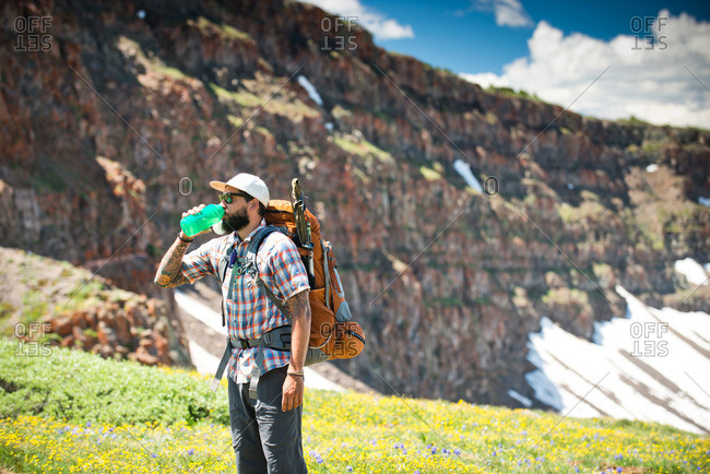 A backpacker takes a water break in the mountains of Yampa, Colorado.
