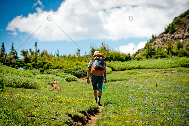 A backpacker hiking through a mountain meadow near The Devil's Causeway in Yampa, Colorado.