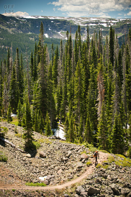 A backpacker hiking down a rocky mountain trail in Yampa, Colorado.
