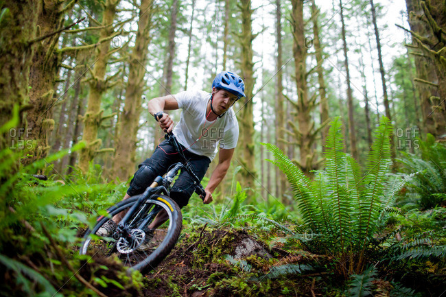 A mountain biker navigates a sharp corner at high speed on a trail that winds through lush forest near Vancouver, Canada.